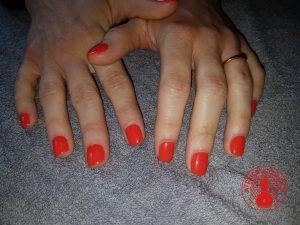 Pose de vernis semi-permanent orange sur les mains réalisée par Laurie Atelier de l'Ongle