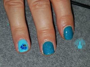 Nail art réalisé par Laurie Atelier de l'ongle réprésentant une fleur bleu accompagné de brillant
